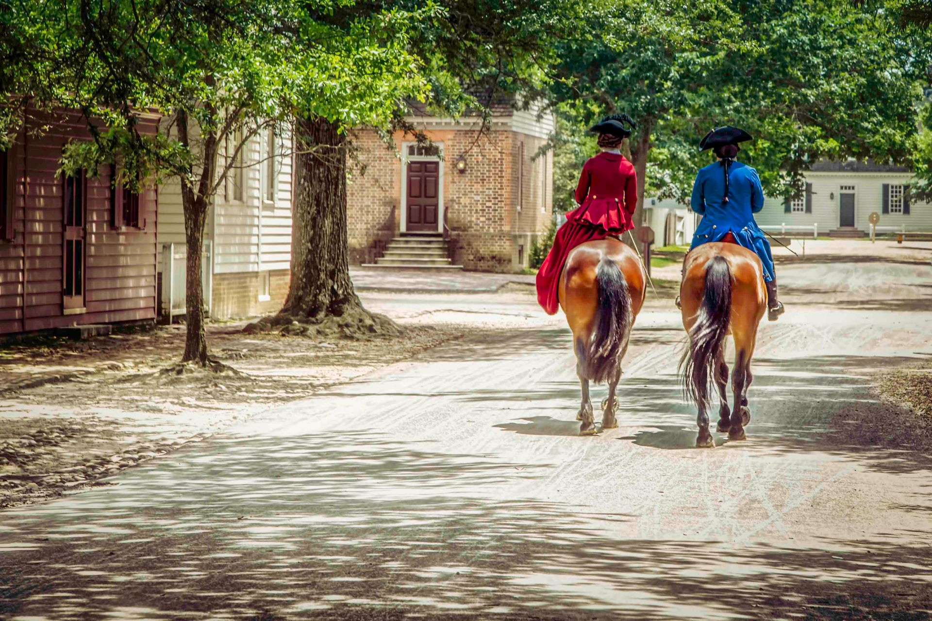 Two residents of Colonial Williamsburg, Virginia on a horseback stroll through town.