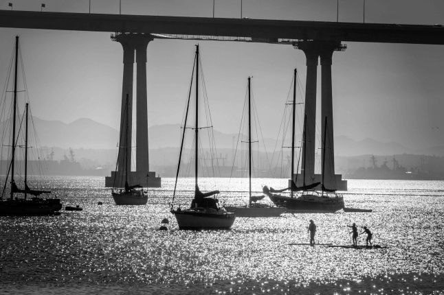 San Diego Bay with sailboats moored, paddle boarders passing by the San Diego-Coronado Bridge, and the shadows of US Navy ships in the background.