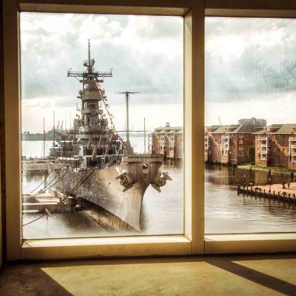 The USS Wisconsin (BB-64) as seen through the window of a parking garage in Norfolk, Virginia.