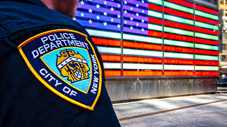 A New York City Police Officer standing in Time Square at the lighted American flag sign on the Armed Forces Recuiting Center.