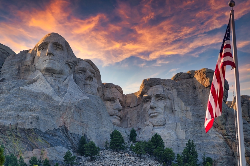 Mount Rushmore with an American flag waving foreground near Keystone, South Dakota.